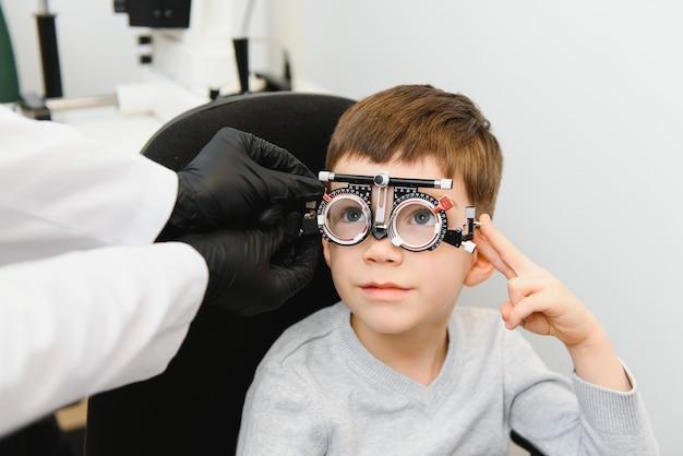 Vrolijk kind jongen in glazen controleert oog visie pediatrische oogarts.
