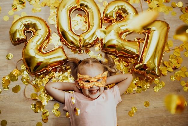 Vrolijk kind meisje in een masker en met de cijfers verheugt zich op de confetti