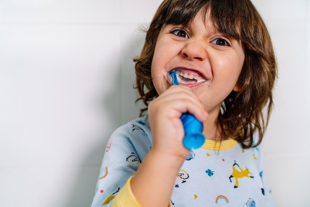 Vrolijk kind zijn tanden poetsen in zijn pyjama's voor het slapen gaan