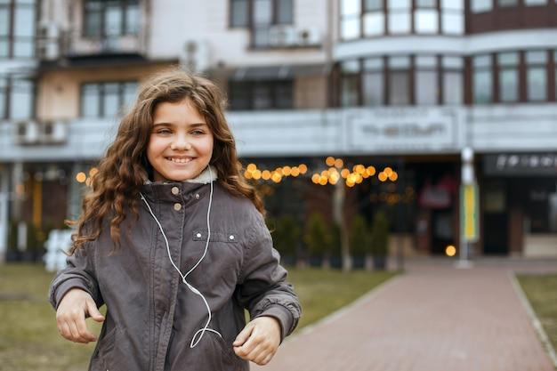 Vrolijk kindmeisje dat muziek luistert in de oortelefoons in de stad. ruimte voor tekst