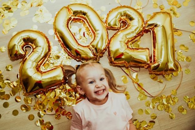 Vrolijk kindmeisje met getallen 2021 verheugt zich in gouden confetti vliegen van bovenaf, bovenaanzicht.