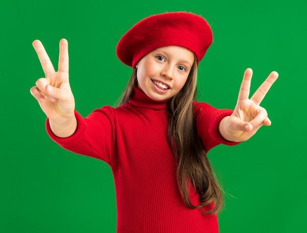 Vrolijk klein blond meisje met een rode baret die een vredesteken toont en naar de voorkant kijkt geïsoleerd op een groene muur