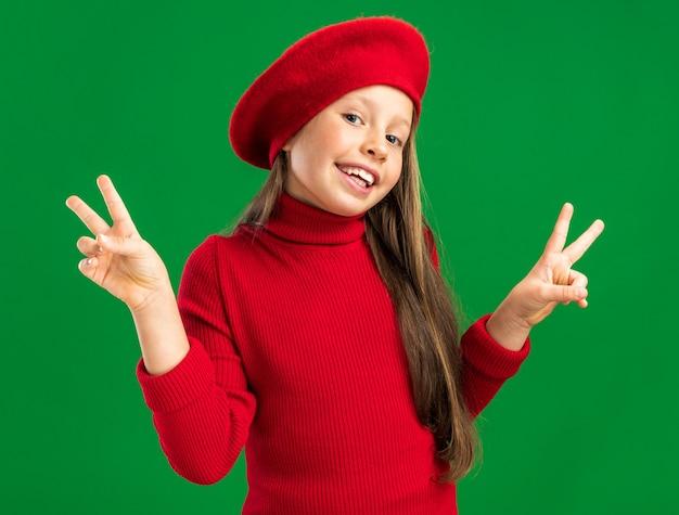 Vrolijk klein blond meisje met een rode baret die naar de voorkant kijkt en een vredesteken toont dat op een groene muur is geïsoleerd