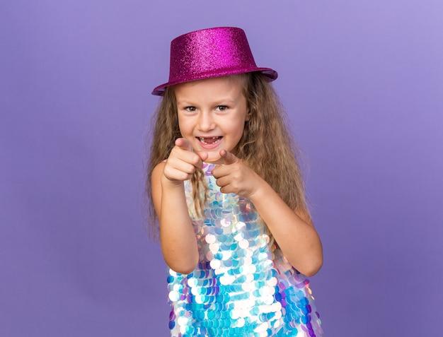 Vrolijk klein blond meisje met violet feestmuts wijzend geïsoleerd op paarse muur met kopieerruimte
