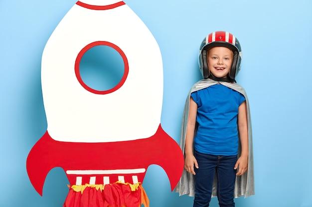 Vrolijk klein kind draagt helm en grijze cape, staat in de buurt van een papieren raket, wil in de ruimte vliegen