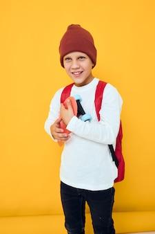 Vrolijk klein kind in een witte trui skateboard entertainment jeugd lifestyle concept
