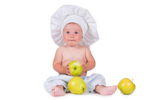 Vrolijk klein kind met appels in handen in een chef-kok pak op een wit.