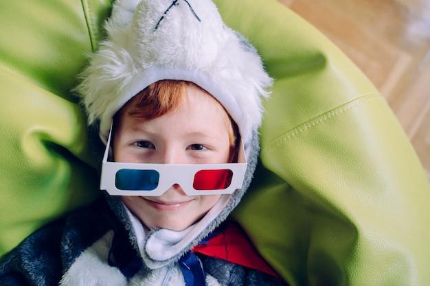 Vrolijk klein kind spelen met driedimensionale bril en interactieve bioscoop thuis. vrije tijd en films concept. portret van kleine jongen die met glazen kijkt. kostuums en grappige activiteiten