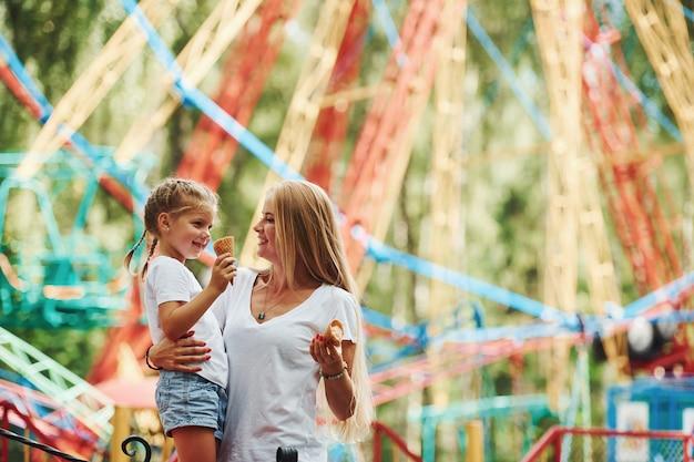 Vrolijk klein meisje haar moeder heeft een goede tijd samen in het park in de buurt van attracties