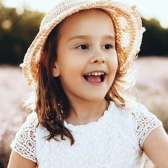 Vrolijk klein meisje met een hoed en een jurk glimlachen terwijl poseren in een veld