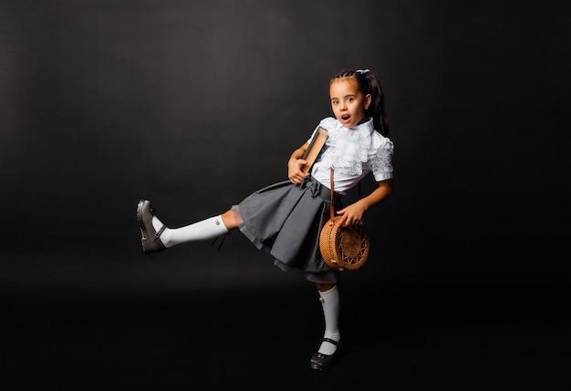 Vrolijk klein schoolmeisje met boek en tas die in het nieuwe seizoen terug naar school gaat, geïsoleerd op een donkere achtergrond