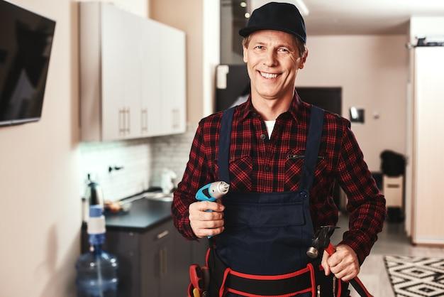 Vrolijk klusjesmanportret van een glimlachende mannelijke voorman die zich met materiaal bevindt