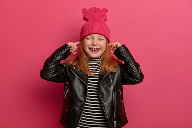Vrolijk knap meisje sluit oren en sluit ogen, lacht positief, negeert luide muziek, komt op kinderfeestje, gekleed in stijlvolle outfit, wil moeder niet horen, stout actief kind zijn