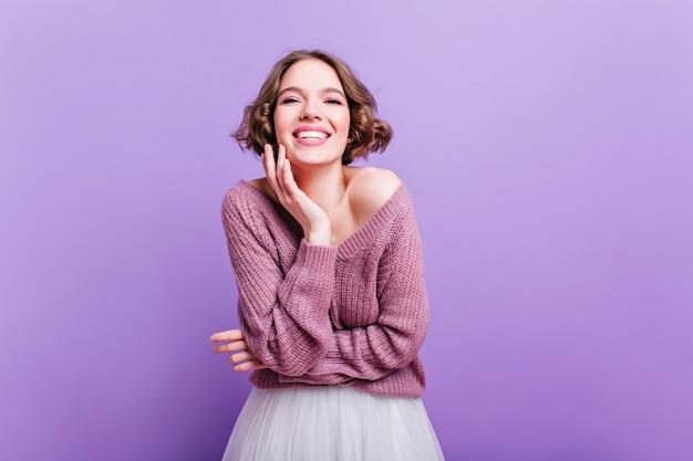 Vrolijk korthaar meisje genieten van fotoshoot in mooie trui. indoor portret van romantische witte dame blij lachend op paarse muur.