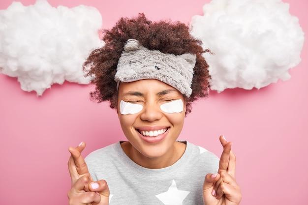 Vrolijk krullend afro-amerikaans meisje hoopt op geluk kruist vingers houdt de ogen gesloten bijgelovig is doet wensen voordat hij in slaap valt draagt slaapmasker pyjama schoonheidspatches vormt binnen