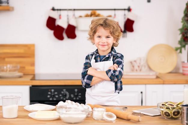 Vrolijk krullend jongetje in schort die de armen op de borst kruist terwijl hij aan de keukentafel staat met ingrediënten voor koekjes