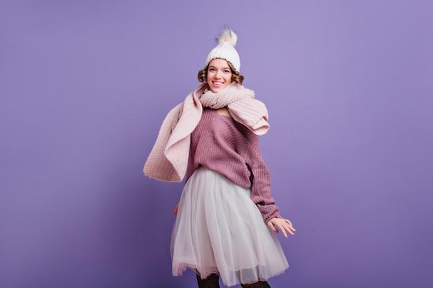 Vrolijk krullend meisje dat in witte hoed geluk op purpere muur uitdrukt. indoor foto van prachtige europese vrouw draagt een lange rok en gebreide sjaal.