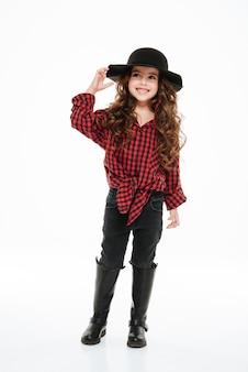 Vrolijk krullend meisje in geruite overhemd en hoed
