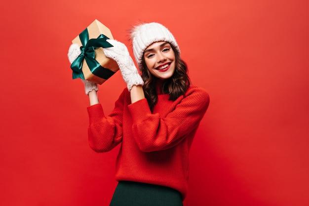 Vrolijk krullend meisje in witte warme muts, wanten en rode trui schudt geschenkdoos en glimlacht op rode muur