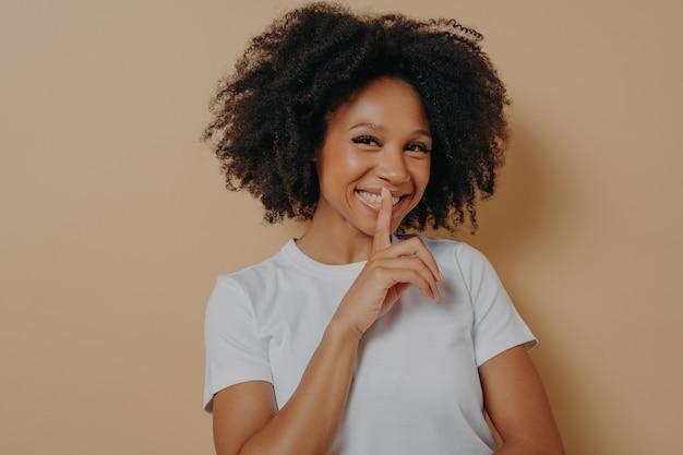 Vrolijk lachend afro-meisje met shhh-teken, houd stiltegebaar, met wijsvinger in de buurt van lippen, staande over pastelbeige achtergrond en camera kijkend. positieve emoties en lichaamstaal