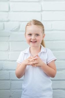 Vrolijk lachend babymeisje portret op een witte muur