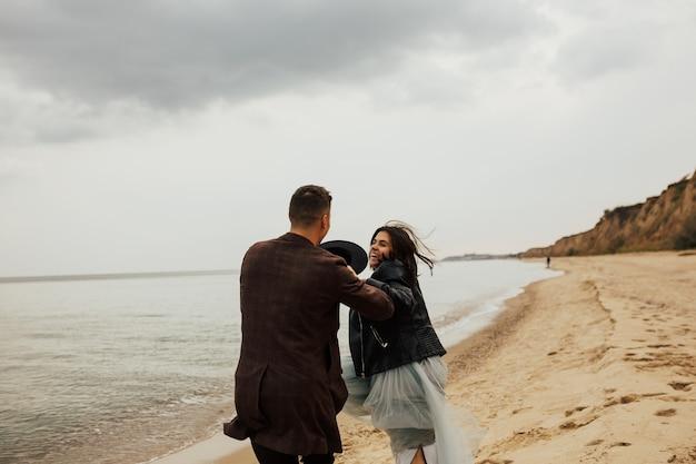 Vrolijk lachend bruidspaar draait op het strand.