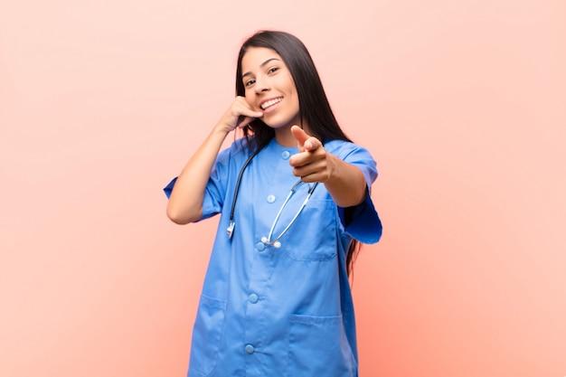Vrolijk lachend en wijzend naar de camera tijdens het bellen van je later gebaar, praten over de telefoon