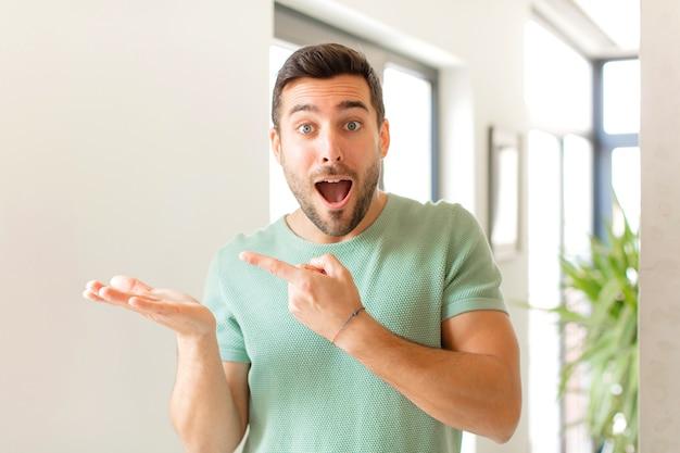 Vrolijk lachend en wijzend naar kopie ruimte op de handpalm aan de zijkant, het tonen of adverteren van een object