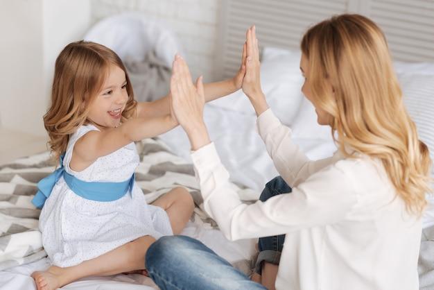Vrolijk lachend meisje dat haar handpalmen tegen de handpalmen van haar moeder drukt en met haar een pat-a-cake-spel voor kinderen speelt.