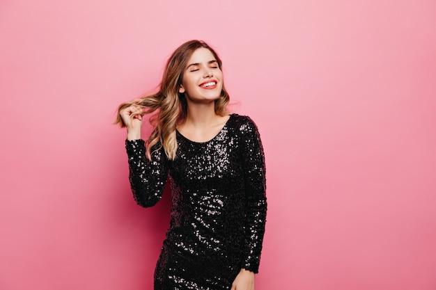 Vrolijk lachend meisje in sparkle jurk genieten van dag. binnen schot van aantrekkelijke jonge dame op roze muur.