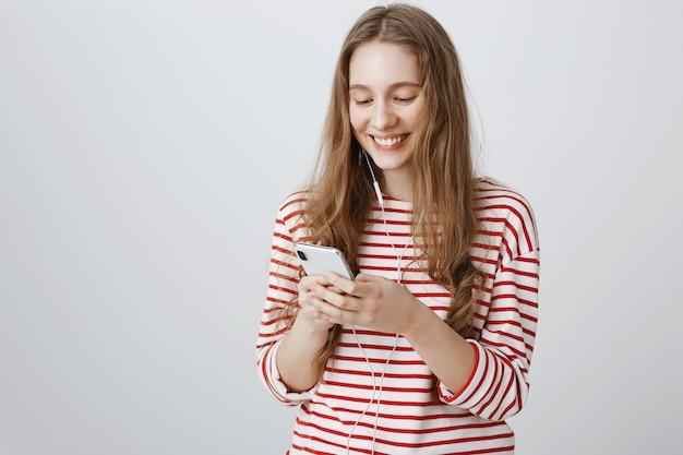 Vrolijk lachend meisje kijken naar het scherm van de mobiele telefoon, oortelefoons dragen