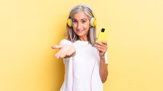 Vrolijk lachend met een vriendelijke, zelfverzekerde, positieve blik, een object of concept aanbiedend en tonend met een koptelefoon