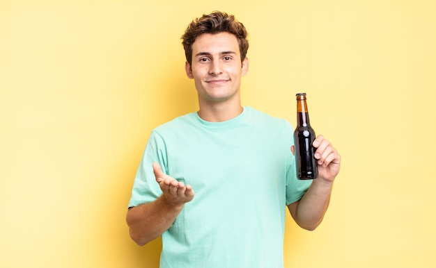 Vrolijk lachend met vriendelijke, zelfverzekerde, positieve blik, aanbieden en tonen van een object of concept. bierfles concept