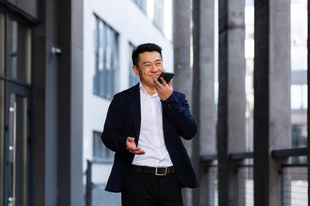 Vrolijk lachend succesvolle aziatische zakenman legt informatie uit aan werknemers die de telefoon gebruiken, spreekt in de buurt van kantoor buiten gelukkig praten