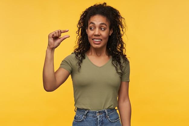 Vrolijk lachende afro-amerikaanse vrouw laat iets kleins zien met haar vingers, voelt zich gelukkig