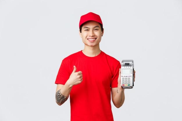 Vrolijk lachende aziatische bezorger raadt het gebruik van creditcards aan, geen contante betaling tijdens covid 19 zelfquarantaine, met betaalterminal pos en duim omhoog, keur contactloze aankoop goed.