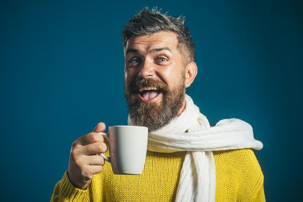 Vrolijk lachende bebaarde man in sjaal en trui houdt kop aantrekkelijke jonge man die geniet van warme koffie