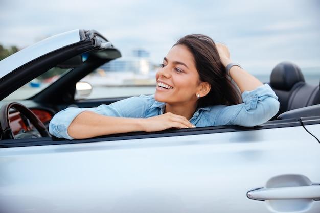 Vrolijk lachende brunette vrouw rusten in haar cabriolet geparkeerd op het strand
