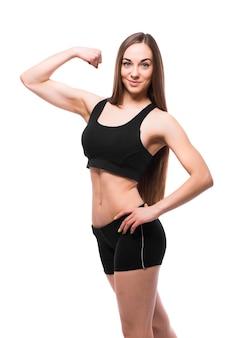 Vrolijk lachende gemengde race sportieve vrouw biceps demonstreren, geïsoleerd op een witte achtergrond
