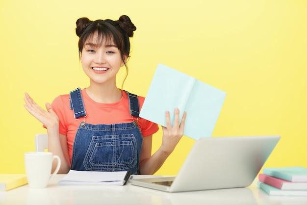 Vrolijk lachende jonge vietnamese vrouw met geopend boek en laptop die online studeert