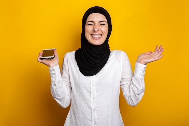 Vrolijk lachende jonge vrouw in hijab met gesloten ogen houdt telefoon op geel.