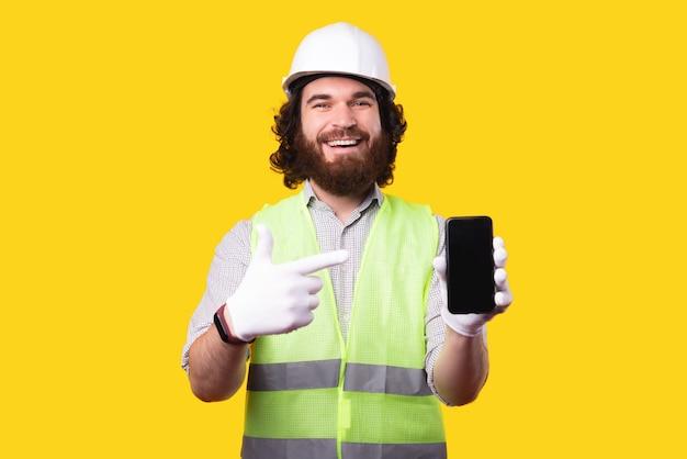 Vrolijk lachende knappe bebaarde architect man wijzend op smartphone