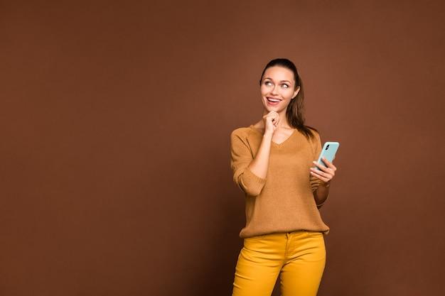 Vrolijk leuk schattig dromerig meisje peinzend kijken naar lege ruimte peinzend over het beantwoorden van ontvangen bericht geïsoleerd