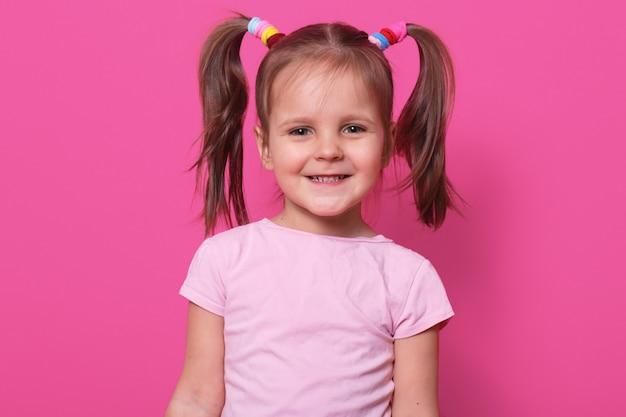 Vrolijk lief klein meisje met grappige staartjes, oprecht glimlachend, rechtop staand, met kleurrijke scrunchies. ruimte voor reclame kopiëren.