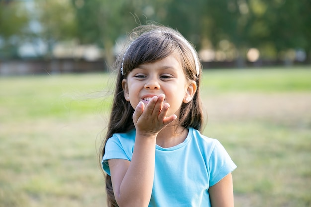 Vrolijk lief zwartharig meisje luchtkus verzenden, poseren in park, wegkijken en glimlachen. jeugd en outdoor activiteiten concept