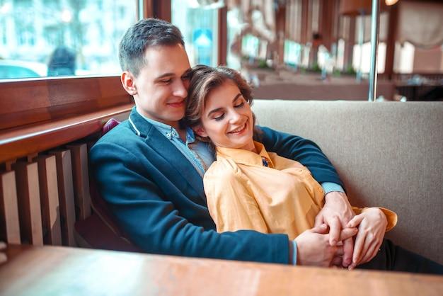 Vrolijk liefdepaar op romantische date. gelukkig man en vrouw knuffels in restaurant.