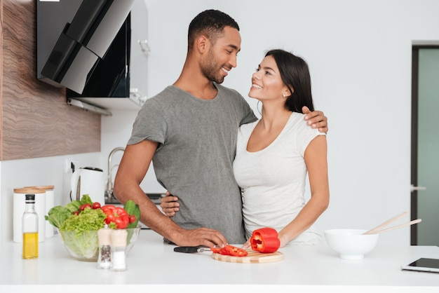 Vrolijk liefdevol paar in de keuken knuffelen tijdens het koken. kijk naar elkaar.