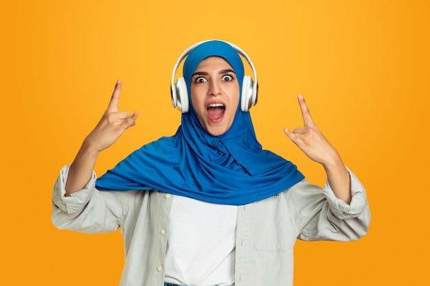 Vrolijk luisteren naar muziek met koptelefoon jonge moslimvrouw op gele muur