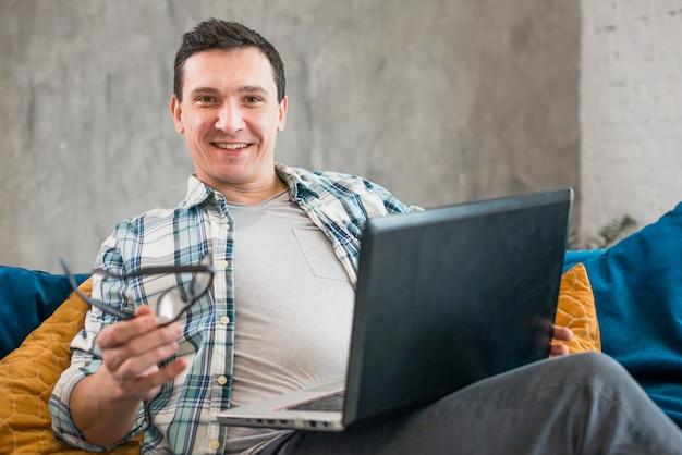 Vrolijk mannetje dat aan laptop thuis werkt