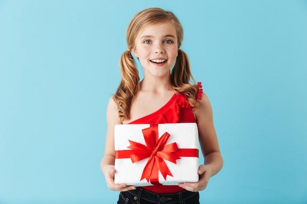 Vrolijk meisje dat een zwempak draagt dat geïsoleerd over een blauwe muur staat en de huidige doos vasthoudt